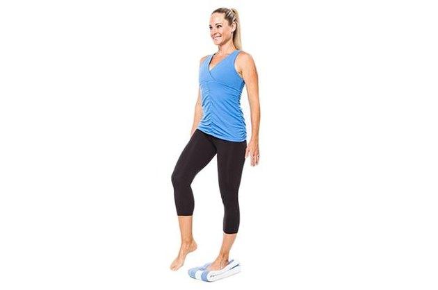 Woman demonstrating single-leg towel balance.