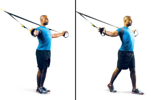 Man performing TRX chest stretch.