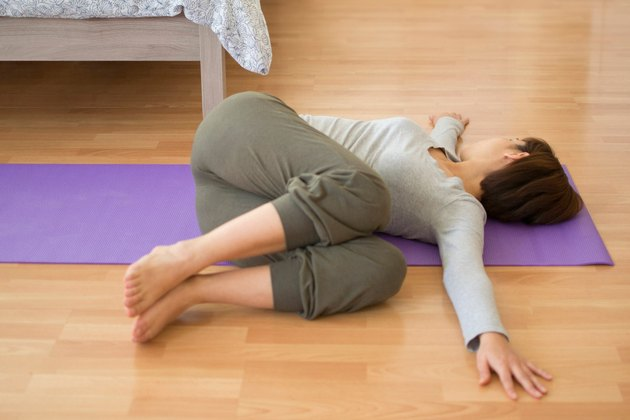 Woman demonstrating how to do Reclined Spinal Twist yoga pose for sleep
