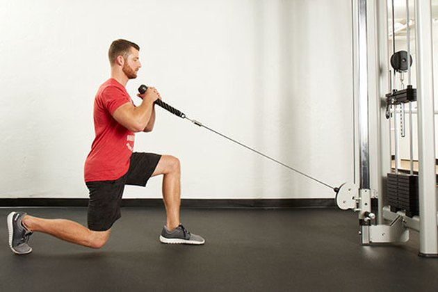 Man performing cable forward lunge on the cable machine