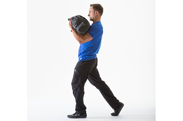 Man doing a Front-Loaded Walk sandbag exercise