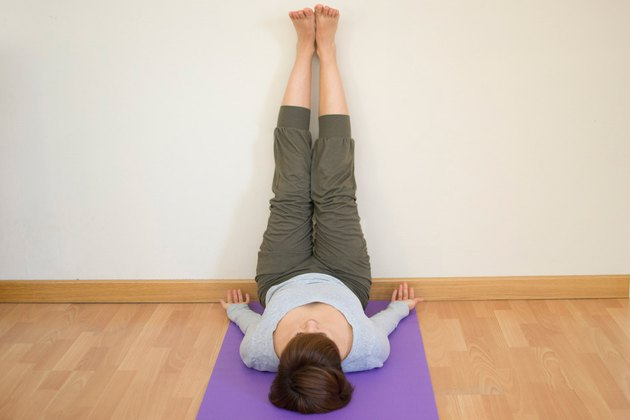 Woman demonstrating how to do Legs-Up-the-Wall pose yoga for sleep
