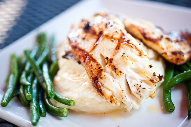 Grilled white fish on top of mashed potatoes and green beans