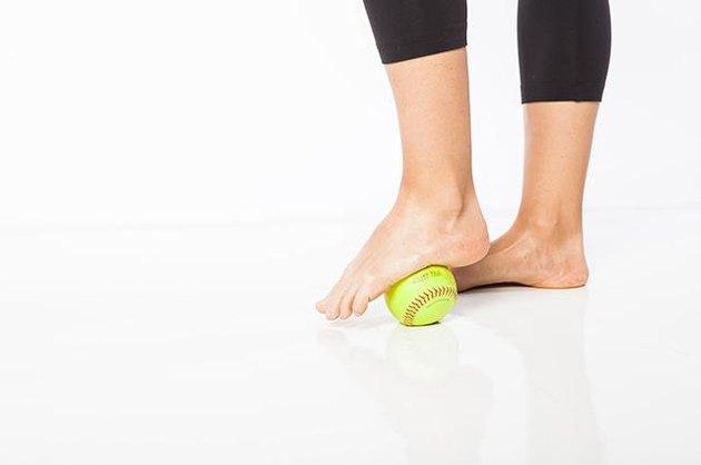 Woman demonstrating standing foot massage.