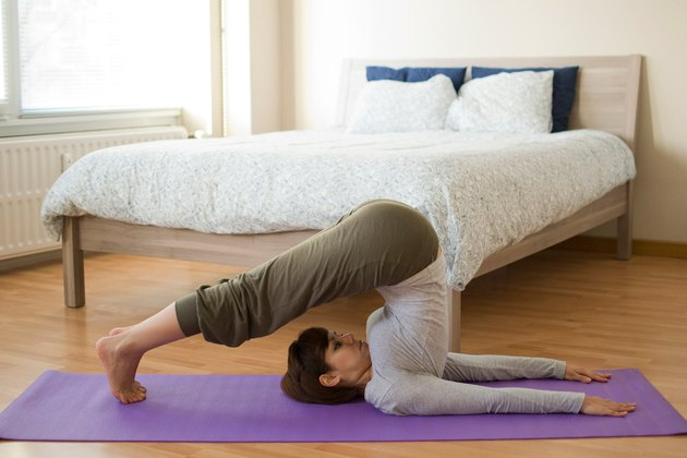 Woman demonstrating how to do Plow pose yoga for sleep