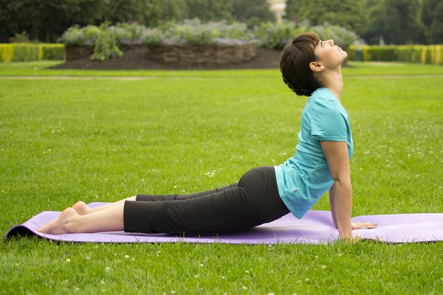 Woman demonstrating how to do the yoga pose Cobra Pose (Bhujangasana)