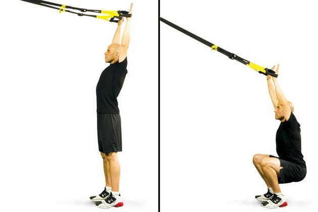 Man performing overhead squat TRX exercise