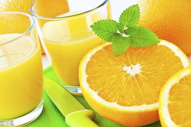 Glass of juice next to an orange