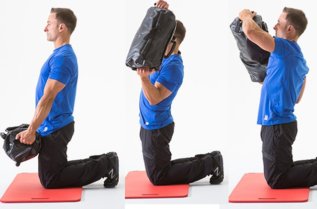 Man doing a Kneeling Around the World sandbag exercise