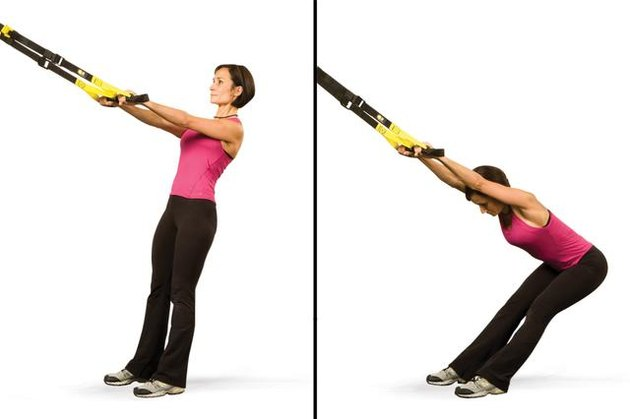 Woman performing lower back stretch TRX exercise