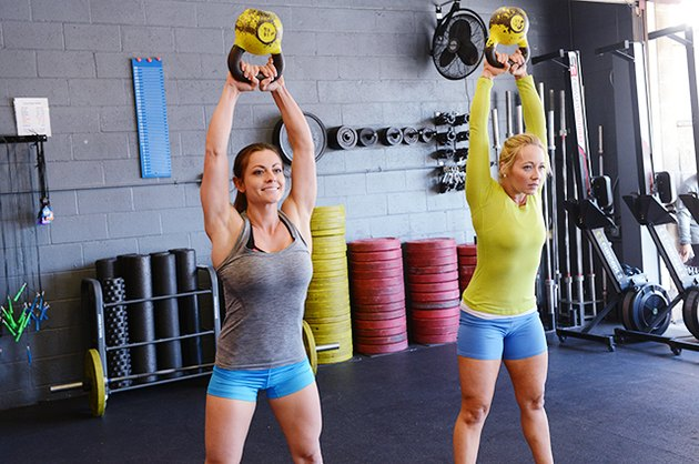 Women performing one of the 16 essential CrossFit moves with kettlebells.