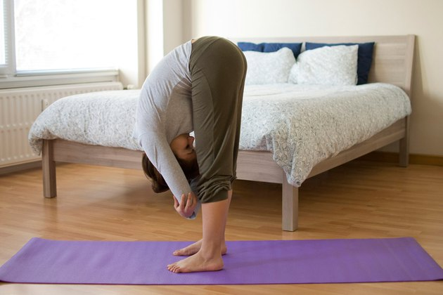 Woman demonstrating how to do Standing Forward Bend yoga pose for sleep
