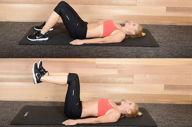 Woman performing leg raise ab exercise.