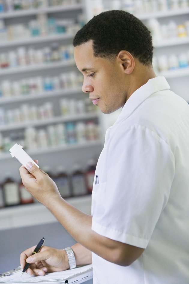 African American male pharmacist with prescription bottle