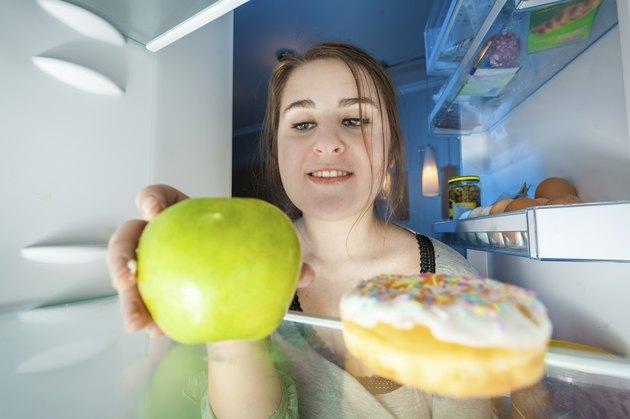 Portrait from inside the fridge of woman taking apple