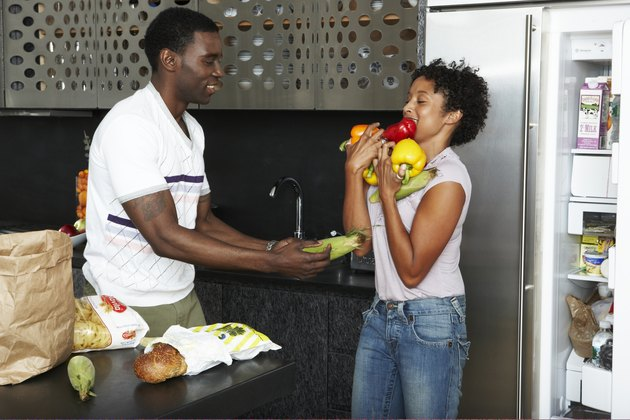 Couple playfully Unpacking groceries in kitchen