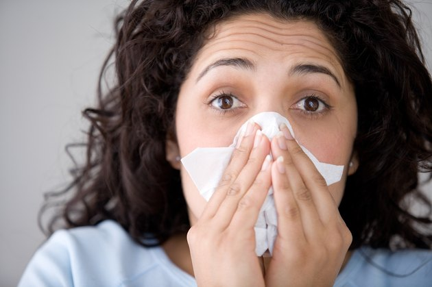 Woman with flu blowing nose