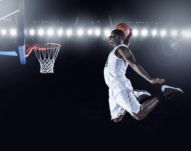 Composite image of basketball player scoring a slam dunk in a professional basketball game.