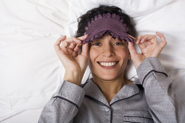 Woman lies with sleeping mask in the bed