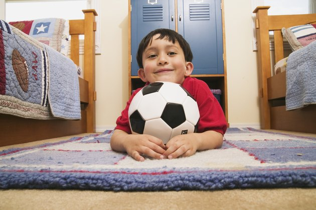 Portrait of a young boy lying on the floor holding a football
