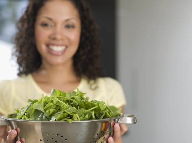 Mixed Race woman holding colander of salad