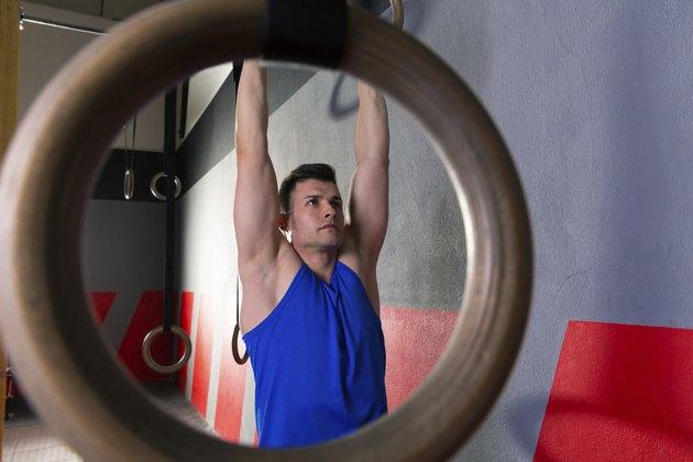 Rings workout man at gym hanging