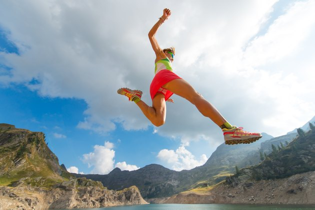 Skipping girl as he runs near a mountain lake