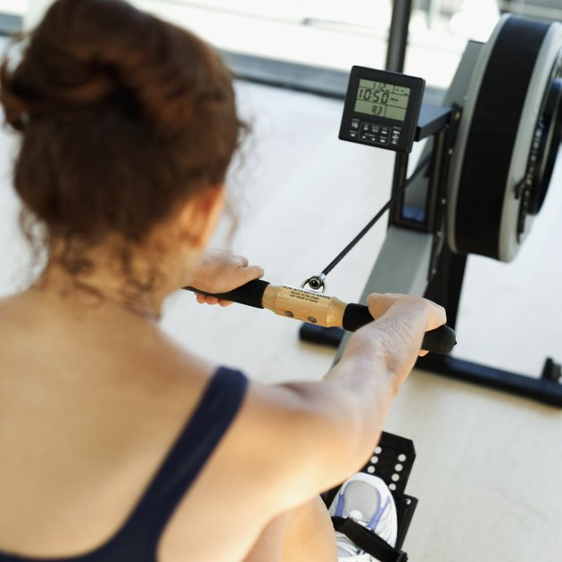 Rear view of a young woman exercising on a rowing machine at the gymnasium