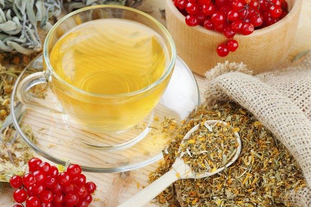 cup of herbal tea, medicinal herbs and healthy berries