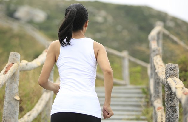 woman runner running at mountain stairs