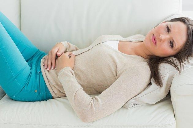 Anxious and sick woman lying on sofa