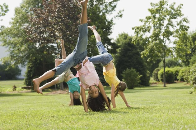 Girls doing cartwheel in field