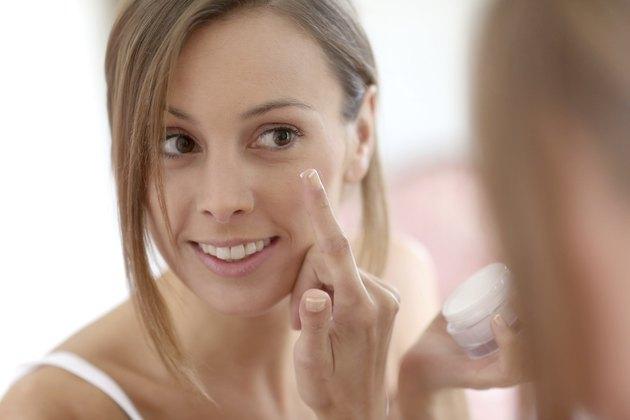 Brunette woman applying cream on face