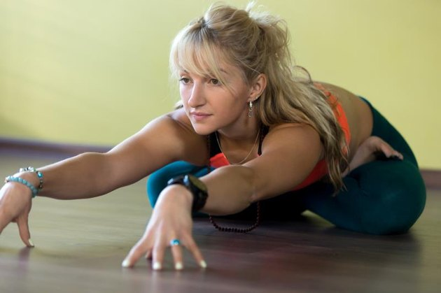 Sporty beautiful blond young woman in sportswear working out indoors, doing variation of Padmasana, sitting cross-legged, bending forward in Lotus Posture, full length