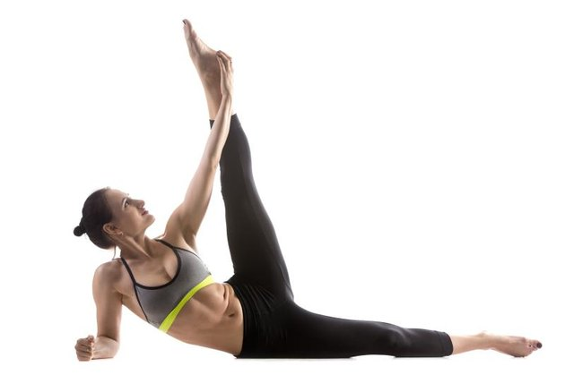 Sporty fit beautiful young woman in sportswear bra and black pants working out, doing Anantasana, Side-Reclining Leg Lift pose, Sleeping Vishnu posture, studio full length, isolated, white background