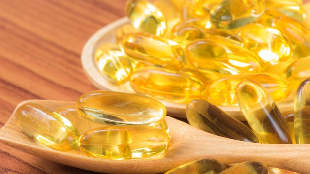 Close-up Fish oil capsules on wooden spoon