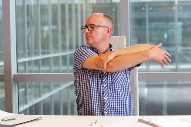 man stretching arm in his office