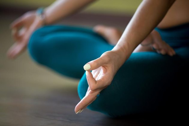 Sporty beautiful woman in sportswear working out indoors, sitting cross-legged in Padmasana, Lotus posture, asana for meditation, breathing exercises, close-up, focus on fingers in Jnana mudra