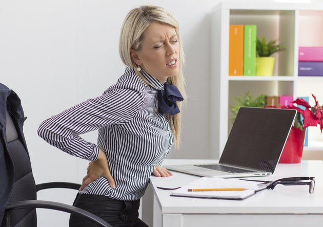 Young woman having back pain at work