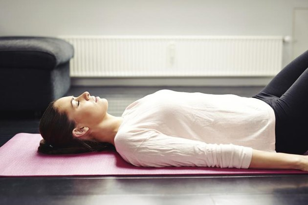 Image of fit young woman relaxing on yoga mat. Female lying on floor - Savasana