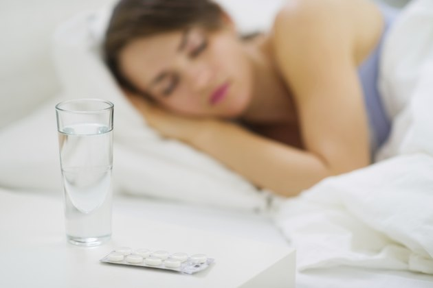 Pills on table and sleeping woman in background