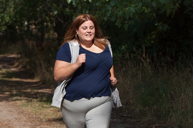overweight woman running outdoors