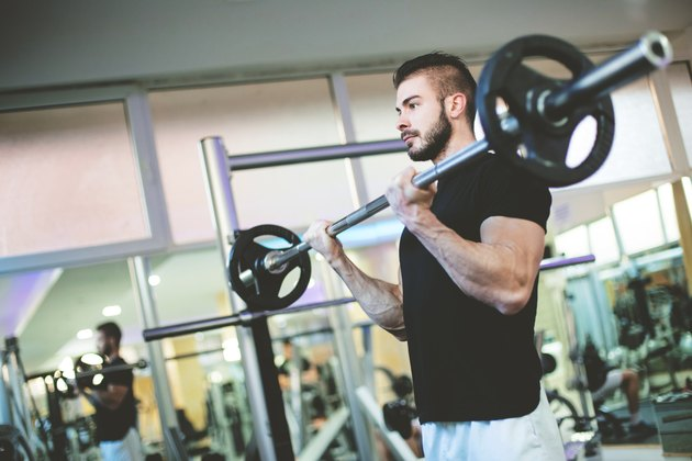 Muscular Bodybuilder Men Doing Exercises with Dumbbells in Gym
