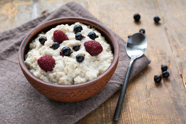 Oatmeal porridge with berries in ceramic brown bowl, close up