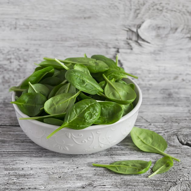 Fresh baby spinach in a white bowl