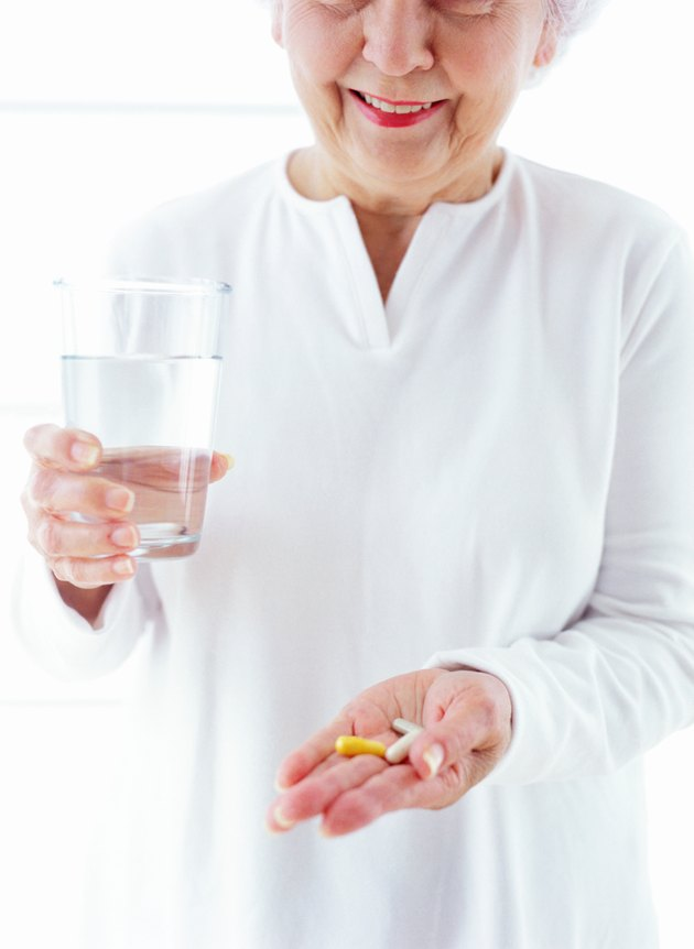 portrait of an elderly woman holding a glass of water and medication