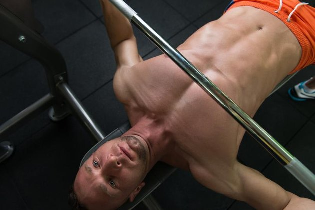 Close-Up Of A Young Man In Gym Exercising Chest On The Bench Press