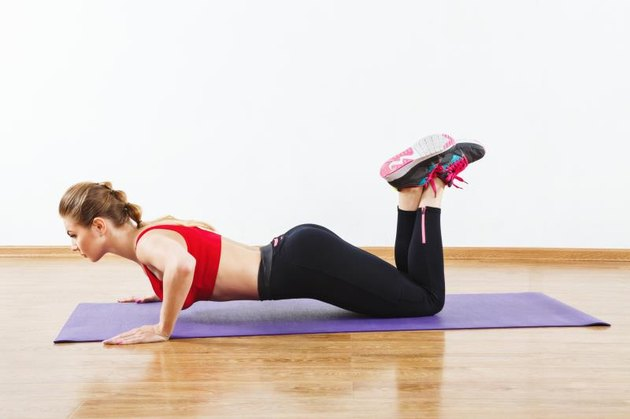 Thin girl with light brown hair wearing snickers, dark leggings and red short top doing push up at gym on purple mat, fitness, white wall and wooden floor.