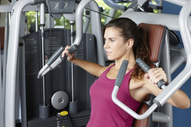 Young woman exercising with machine