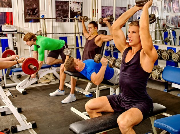 Group of men working his body at gym